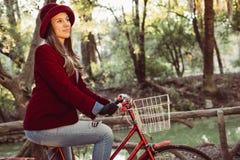 Mujer en bici del montar a caballo de la moda del vintage el día de la caída Imagen de archivo