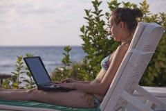 Mujer en bikiníes con la computadora portátil foto de archivo libre de regalías