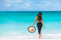 Mujer en bikini negro y los sarong que se colocan en la playa Imagen de archivo libre de regalías