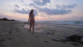 Mujer en bikini que camina en la playa del mar almacen de video