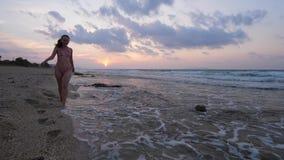 Mujer en bikini que camina en la playa del mar en la puesta del sol metrajes