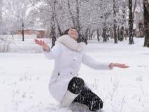 Mujer en blanco y nieve que cae Imagenes de archivo
