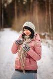mujer en bosque del invierno en una chaqueta rosada Imágenes de archivo libres de regalías