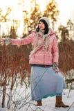 mujer en bosque del invierno en una chaqueta rosada Foto de archivo libre de regalías