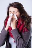 Mujer en bufanda que estornuda Imagen de archivo libre de regalías