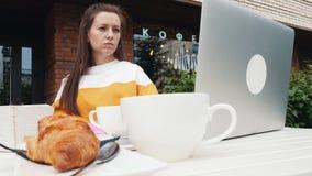 Mujer en café al aire libre con el ordenador portátil almacen de metraje de vídeo