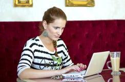 Mujer en café con la computadora portátil Fotos de archivo libres de regalías