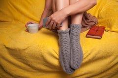 Mujer en calcetines hechos punto en el sofá que se relaja Imágenes de archivo libres de regalías