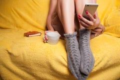 Mujer en calcetines hechos punto en el sofá que se relaja Fotografía de archivo libre de regalías