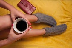 Mujer en calcetines hechos punto en el sofá que sostiene una taza de café Imagen de archivo libre de regalías