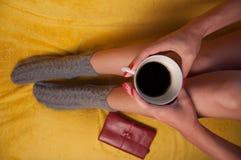 Mujer en calcetines hechos punto en el sofá que sostiene una taza de café Imagenes de archivo