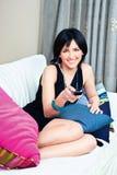 Mujer en cama con el control remoto Imágenes de archivo libres de regalías
