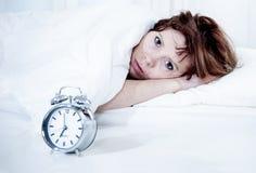 Mujer en cama con el insomnio que no puede dormir el fondo blanco Fotografía de archivo libre de regalías
