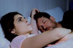 Mujer en cama con el novio que piensa en la relación mientras que el hombre está durmiendo en la noche imagenes de archivo