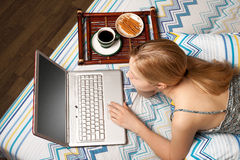 Mujer en cama con la computadora portátil Imágenes de archivo libres de regalías