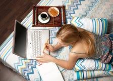 Mujer en cama con la computadora portátil Fotos de archivo