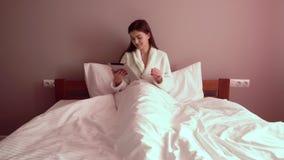 Mujer en cama con la tableta almacen de metraje de vídeo