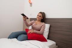 Mujer en cama con teledirigido Fotos de archivo libres de regalías