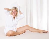 Mujer en cama con una almohada grande Imágenes de archivo libres de regalías