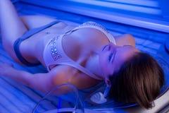 Mujer en cama que broncea Imagen de archivo