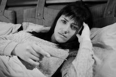 Mujer en cama que comprueba el termómetro de la tenencia de la temperatura blanco y negro imagen de archivo libre de regalías