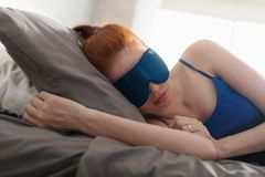 Mujer en cama que duerme con la máscara del sueño en ojos fotos de archivo libres de regalías