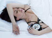 Mujer en cama que duerme con un reloj de alarma Fotografía de archivo