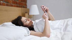 Mujer en cama que hojea en Smartphone en la noche almacen de video