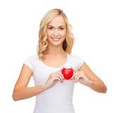 Mujer en camisa blanca en blanco con el pequeño corazón rojo Foto de archivo