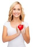 Mujer en camisa blanca en blanco con el pequeño corazón rojo Imágenes de archivo libres de regalías