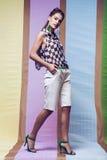Mujer en camisa del ajedrez y pantalones cortos en los talones en fondo multi Imagen de archivo libre de regalías
