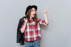 Mujer en camisa del sombrero y de tela escocesa que señala el finger lejos Imagen de archivo