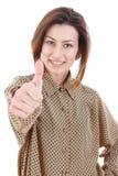 Mujer en camisa marrón y vaqueros que presentan en blanco y que muestran el pulgar Imagen de archivo