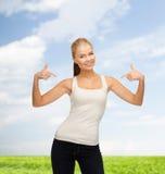 Mujer en camiseta blanca en blanco que señala en sí misma Imágenes de archivo libres de regalías