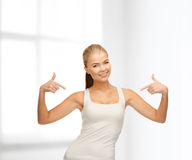 Mujer en camiseta blanca en blanco que señala en sí misma Imagenes de archivo