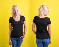 Mujer en camiseta con cuello de pico negra en fondo amarillo Foto de archivo