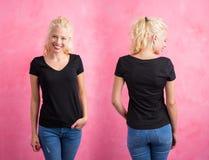 Mujer en camiseta con cuello de pico negra en fondo rosado Imágenes de archivo libres de regalías
