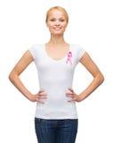 Mujer en camiseta en blanco con la cinta rosada del cáncer Imagen de archivo libre de regalías