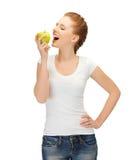 Mujer en camiseta en blanco que come la manzana verde Imagen de archivo libre de regalías