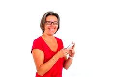 Mujer en camiseta roja en smartphone en estudio imagenes de archivo