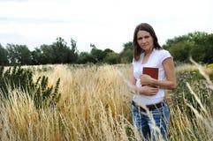 Mujer en campo con el libro Fotos de archivo libres de regalías