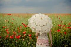 Mujer en campo de las amapolas con el paraguas Filtro artístico aplicado Imagen de archivo libre de regalías