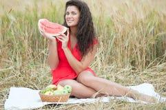 Mujer en campo de trigo que come la sandía. Comida campestre. Imágenes de archivo libres de regalías