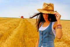 Mujer en campo del centeno delante de la cosechadora Foto de archivo