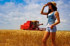 Mujer en campo del centeno delante de la cosechadora Fotografía de archivo