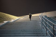 Mujer en capa que camina abajo de las escaleras Foto de archivo libre de regalías