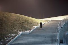 Mujer en capa que camina abajo de las escaleras Fotos de archivo