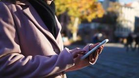 Mujer en capa que llama el taxi vía el app en línea en el teléfono celular, usando la navegación de los gps almacen de metraje de vídeo