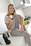 Mujer en casa que come café Imagenes de archivo