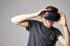 Mujer en casa que lleva las auriculares de la realidad virtual que juegan al juego fotografía de archivo